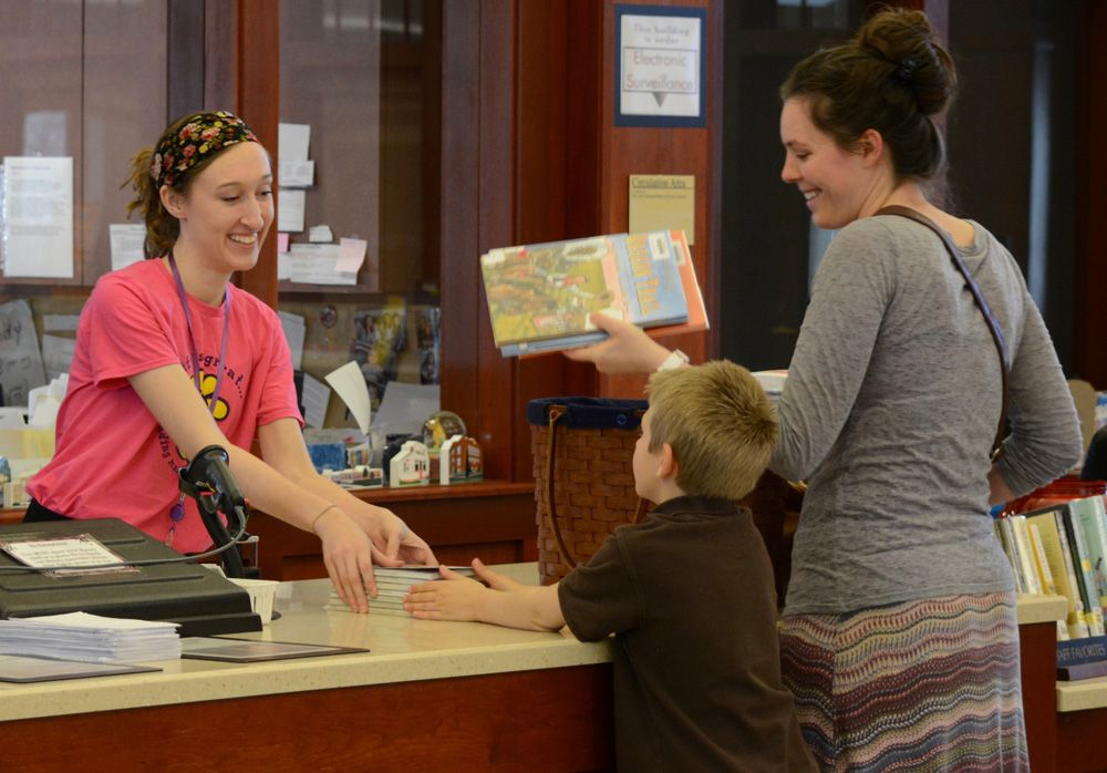 Library staff checking out books to a mom and child.