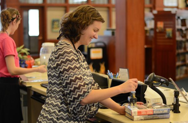 library staff stamping the due date on books